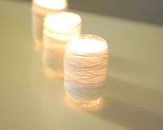 Yarn wrapped votive candles, modern, vintage?, structured wedding idea.