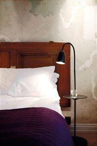 Bedroom in Story Hotel, Black Arkipelag floor lamp with table from Rubn, design by Niclas Hoflin