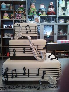 3-tier square music themed cake covered in white fondant icing, decorated with sheet music lines. No Saxes for the b'day.