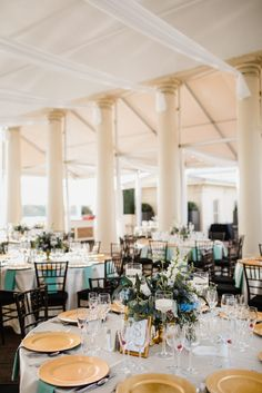 Draping and round table arrangement with garden chairs and gold chargers at Philadelhpia Water Works wedding. Green, blue, purple and white floral centerpieces by Robertson's Flowers & Designs and photo by Love Me Do Photography. Full wedding shared on Flutter Social.