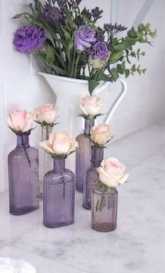 Purple glass bottles with pink roses. Lovely.