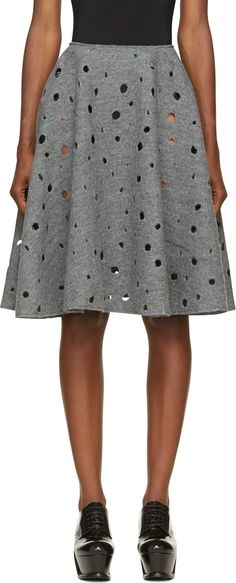 Wool circle skirt in grey melange. Holes in various sizes throughout. Concealed zip closure at side. Unlined. Tonal stitching.
