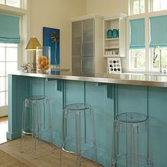 An emphasis on color and light enhances this kitchen's coastal feel. Don't be afraid to use strong color in big, unexpected ways such as on your kitchen island. So this island doesn't seem stark and alone in the middle of the room, the same color was repeated in simple window shades. Plenty of sunlight, additional white cabinetry, and warm wood floors balance the bright aqua.