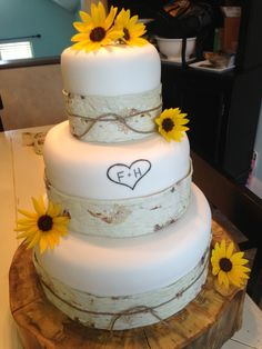 Fall wedding cake.Take away sunflowers and replace with ice glazed oak leaves.Or a flower from bouquet