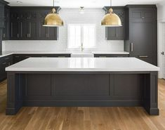 Kitchen with black cabinets, white counters, white walls, and a white backsplash. Here are 10 home design trends to expect in Dark Grey Kitchen Cabinets, Black Kitchen Cabinets, Farmhouse Kitchen Cabinets, Grey Kitchens, Painting Kitchen Cabinets, Kitchen Cabinet Design, White Cabinets, Inset Cabinets, Kitchen Paint