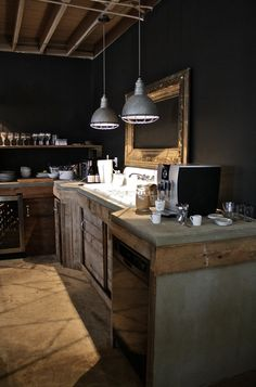 rustic industrial kitchen with black walls, concrete counters
