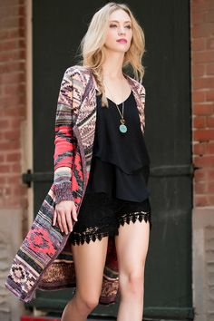 """Throw on the Zaragoza Long Sweater Wrap for a statement of color & print. A vivid tribal print decorates this long cascading sweater wrap. Style over anything from a bodycon dress to a pair of jeans & boots!<br /> <br /> - 43"""" length from shoulder to hem<br /> - 10"""" chest<br /> - measured from a size small<br /> <br /> - 75% Acrylic, 25% Wool<br /> - Hand Wash<br /> - Imported"""