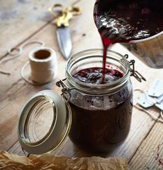 Jam being poured into a glass jar from a stainless steel pot.