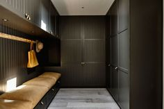 In this modern mudroom, large overstuffed light brown leather pillows cushion the built-in bench with storage, while black cabinets with leather drawer pulls provide plenty of storage and organization opportunities. For hanging hats and bags, there's a simple light wood wall mounted coat rack.