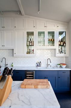 Dark blue lower cabinets, white upper cabinets and subway tiles with (I think) light gray grout.