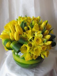 daffodils and tulips. cheerful. Cast iron plant leaves, curled & pinned.