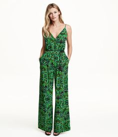 CONSCIOUS. Sleeveless jumpsuit in woven fabric with narrow shoulder straps, V-neck front and back, wrapover front, and hook-and-eye fastener at top. Seam at waist, side pockets, and wide, straight legs. Matching, twisted tie belt with tassels on ends. Unlined. Made partly from recycled polyester.