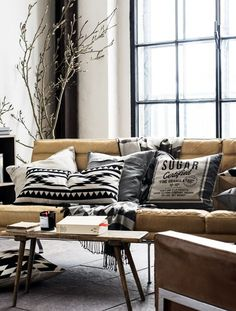 Lounge colour palette inspo: bw cushions on brown leather couch.