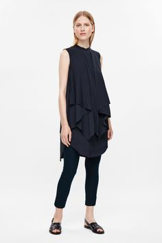 This sleeveless dress is made from a soft cotton poplin with chunky draped layers. A relaxed fit, it has a neat grandad collar, side-seam pockets and a  front placket with hidden shirt buttons.