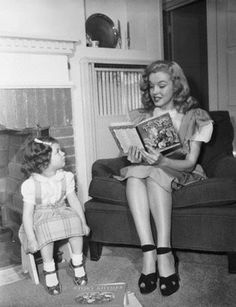 Photo of a young Marilyn Monroe reading aloud to a child.