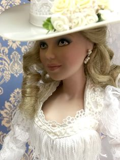 """Annie Rose,  The Western Bride Doll. An all-American, high-spirited Western bride on her special day—ready to take the biggest two-step of her del Sculptured in fine porcelain, she has exquisite hand-painted features. Her soft blonde hair is styled in a cascade of curls. Dressed in pristine white floral jacquard and chiffon trimmed in white one and sassy fringe at the bodice. The dress is tradi-tionally cur shorter in front to show off her wedding boots. Approx. 16"""" ( cm  41,6)"""