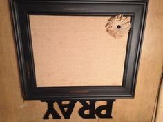 """Prayer Wall. 18x20 cork board covered with burlap. Used Krylon High Strength Spray Adhesive to mount burlap to cork board. Used 1/8"""" offset clips to secure board to frame. Got open black frame on sale at Michael's. The burlap flower caught my eye so I grabbed it for an accent. Found the PRAY scroll at Hobby Lobby. Now we can pin any prayer concerns up in a visible spot. Yay!"""