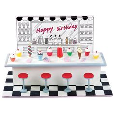 """Malt Shoppe Memories Cake - Our fondant soda fountain really takes you back. It's definitely a """"conversation cake,"""" thanks to great details like the hand-cut tile floor, lollipop stick stools and cool ice cream treat candles."""