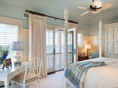 Calm, clean, fresh and lovely beach bedroom.  I love the shutters, the pale blue ceiling partway down the wall to meet white beadbord, the uncanopied bedposts, so much white, and the only pattern in a soft blanket.