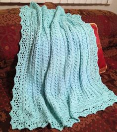 This textured baby blanket features a lacy, scalloped trim