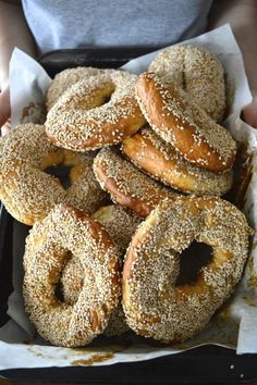 HOMEMADE MONTREAL BAGELS ==    1 1/2 c warm water, 2 pkg instant yeast, 1 t sugar, 1 1/2 t salt, 1 egg, 1 egg yolk, ¼ c oil, ½ c honey, 5-6 c bread flour, 1/4 c barley malt syrup (honey can also be substituted), 1 ½ c lightly toasted sesame seeds ====