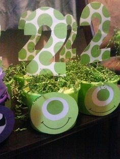 Monsters Inc party - Mike Wezowski Centerpiece. These were so easy and fun to make. Plastic bucket, crinkled paper grass, and cardstock paper.