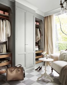 So much to love about this walk-in closet: the custom built-in wardrobes painted a lovely grey, the floor to ceiling window that allows for abundant natural light, the glamorous chandelier, drapery and seating…