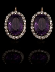 Pair antique amethyst and diamond cluster earrings, each set with a large oval cut amethyst measuring approx 15mm x 11mm in claw setting surrounded by twenty-one old cut diamonds in galleried white metal claw setting on yellow metal back with yellow metal clips, 20mm x 15mm.