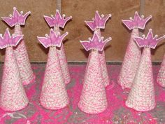 Take a pastry brush and paint the royal icing onto upside down sugar cones. Sprinkle pink sprinkles onto the iced cones and allow them to dry.     Use kitchen shears to cut the tips off of the cones so there is a hole at the top of each one.