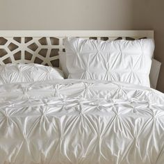 I would love to have a bed full of white bedding, but alas, I own a dog who sleeps on the bed!  (West Elm's organic cotton pintuck duvet)