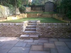 Sandstone paving London brick retaining walls with steps/new lawn and soft wood sleeper retainers