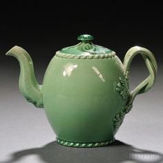 Staffordshire Cream-colored Earthenware Teapot and Cover, England, c. 1775, barrel shape with gadrooned rim and foot, entwined strap handles terminating at flowers and leaves, press-molded leaves to