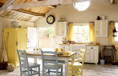 John Lewis of Hungerford Kitchen Design.....a beautiful, cheerful, sunny yellow English Cottage Kitchen, whitewashed floors, white painted brick walls. yellow cabinet, i like the addition of the light blue chairs into the yellow color scheme