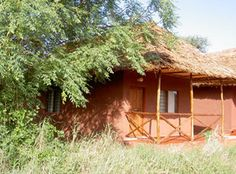 Red Elephant Safari Lodge is situated at the gate of Tsavo East National Park. just outside the town of Voi.     There are 15 guest rooms, built of local stone with makutu roofs. Each room is self-contained with bathroom with shower, flush WC., hot and cold water is available. The windows are covered by mosquito-wire to protect guests of insects and nets are provided.     The main building is covered by a big makuti roof. A mixture of European and African Cusine in fresh quality is offered. Water Catchment, Guest Rooms, Beautiful Landscapes, Gazebo, Safari, Insects, National Parks, Elephant