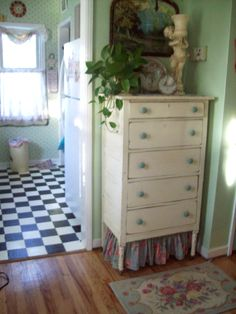 here's a storage idea...i put my gallon water jugs under the curtains i've applied to this little dresser...