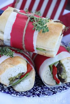Flank Steak Sandwiches on baguettes wrapped in red & white paper tied with string.