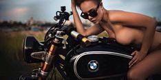 Modelo sexy posa desnuda en una moto BMW clásica