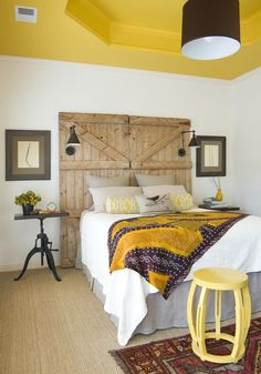 Gorgeous sunny yellow ceiling in this great bedroom. Love the barn door headboard, industrial nightstands and wall sconces as well.