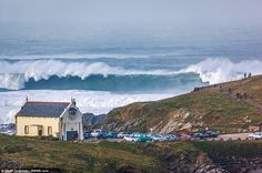 Incoming: Giant waves batter the coastline at Towan Headland, Newquay, near the old lifeboat station