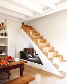 Originale scala rustica realizzata in muratura con i gradini in legno. L'inserimento della panca sottoscala rende lo spazio molto confortevole, ideale per leggere dei libri o rilassarsi.