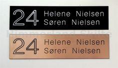 Postkasseskilt med husnummer og navne på beboere.