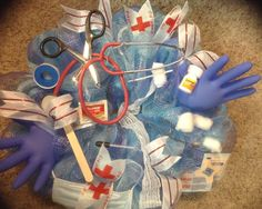 Deco mesh wreath with a medical theme. Mesh is blue/purple and embellished medical gloves, stethoscope, tongue depressor,thermometer, band-AIDS, gauze, surgical scissors & clamps, cotton balls, eye dropper, and white ribbon