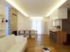 Mennyezeti rejtett világítás egy családi házban - a meleg fehér színhőmérsékletű fénytől bensőségesebb az egybenyitott tér.