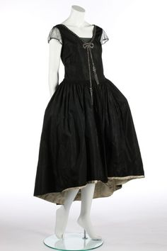 Kerry Taylor Auctions A black taffeta robe de style, circa 1926. with rhinestone and seed-beaded trompe l'oeil bow to the bodice front, shirring to waist, tulle puff sleeves, the hem faced in ivory taffeta, with integral black taffeta hooped panniers, bust 92cm, 36in; together with a dark brown satin dress c.1918-20, labelled 'Ferle Heller', with tiered skirt and trimmed with ribbons (2). - See more at: http://kerrytaylorauctions.com/one-item/?id=61&auctionid=401#sthash.MKtkL5uK.dpuf