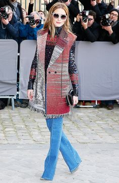Olivia Palermo wears a turtleneck sweater, red fringe vest and light-wash flare jeans