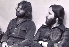 Founding Beach Boys Dennis Wilson and baby brother Carl Wilson idly shoot the breeze while waiting to take the stage, circa 1973.