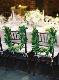 Bride & groom chairs wrapped in beautiful garland.