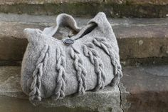 Knit this accessory felted bag from Rowan Knitting & Crochet Magazine 52 online, a design by Sarah Hatton using the beautiful yarn British Sheep Breeds Boucle (wool). With a long strap and cable effect front pieces, this knitting pattern is for the intermediate knitter and is a free pattern to download.