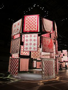 Defying gravity, the quilts appear to spiral in mid-air, creating circular pavilions. Massage Room Design, Scarf Display, Textile Museum, Textile Art, Showroom Interior Design, Two Color Quilts, Red And White Quilts, Textiles, Stand Design