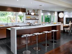 To pay homage to the home's mid-century modern design, the kitchen layout maximizes the outdoor view and features streamlined zebra-wood cabinetry with white quartz countertops.